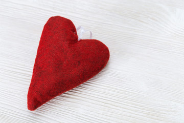 One red fleece heart on white wooden background. Handmade soft toy heart. Selective focus and copy space for text