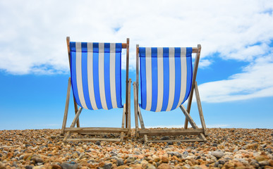two wooden deck chairs at the beach