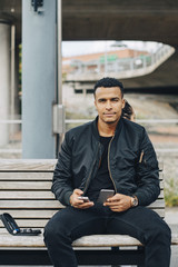 Portrait of man holding glaucometer and smart phone while sitting on bench