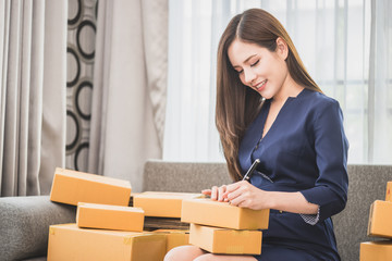 Small online business owner is writing package for delivery