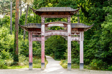 The old wooden chinese gate in the garden of tropical agronomy in Paris has lost its original red color because of the action of sunlight and rain.