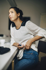 Thoughtful businesswoman injecting insulin while sitting on chair at table