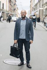 Full length of smiling mature businessman standing on city street