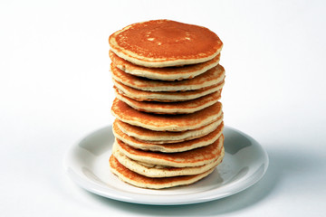 Tall stack of pancakes set against a white background