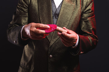 Magician shows trick with a fake finger. Manipulation with props. Sleight of hand.