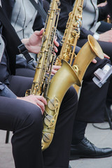 Saxophonists playing in a jazz band, dressed in men's classic vest and trousers. Close up shoot of hands