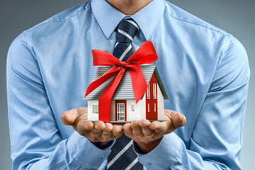 Worker in blue shirt holding house with red ribbon. Close up. Business concept