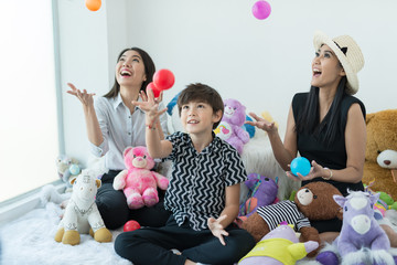Three brethren playing with colorful plastic balls at home