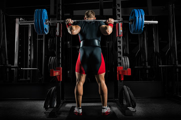 Professional athlete is standing with a barbell on his shoulders and is about to sit down with her.