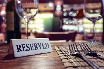 Door stickers Restaurant Reserved sign on restaurant table with bar background