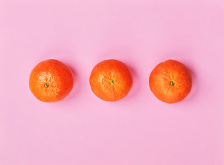 Three orange tangerines isolated on hot pink background. Copy space. Flat lay. Healthy eating