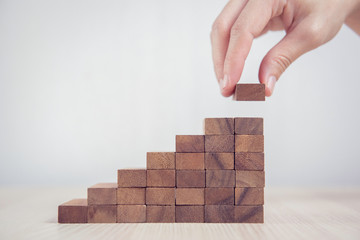 Close up Woman hand arranging wood block stacking as step stair. Business concept growth success...