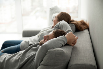 Relaxed couple asleep resting or having nap sitting on comfortable sofa enjoying daytime doze on weekend, calm carefree man and woman relaxing sleeping leaning on couch in cozy living room together Fotomurais