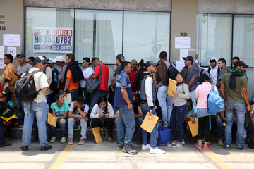 Venezuelan citizens queue to get their temporary residence permit in Lima