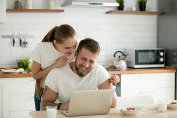 Happy young couple using laptop in the kitchen before having breakfast together in the morning, smiling man and woman looking at computer screen checking latest news online in social networks