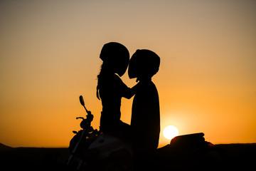 silueta de pareja encima de la moto con sol detras