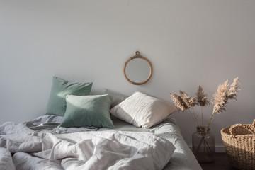 Schlafzimmer mit Bett und Spiegel an der Wand, Korb und Dekoration
