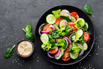 Healthy vegetable salad of fresh tomato, cucumber, onion, spinach, lettuce and sesame on plate. Diet menu. Top view. - fototapety na wymiar