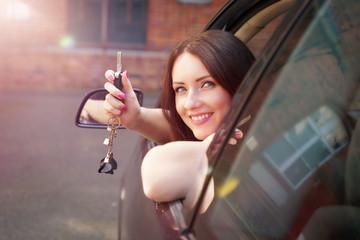 Frau hält Autoschlüssel aus dem Fenster