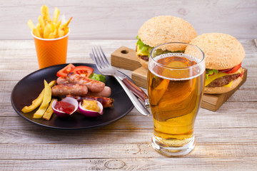 Glass of beer with sausage plate, burgers and fries on wooden background. Beer and food concept. Ale and food, horizontal