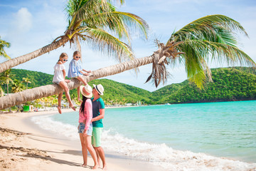 Kids having fun sitting on the palm tree. Happy family relaxing on tropical Carlisle bay beach with white sand and turquoise ocean water at Antigua island in Caribbean