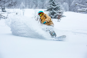Fototapete - A snowboarder girl is riding down the hill. Powder day in mountains.