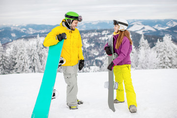 Young couple having fun standing with snowboards during the winter vacation on the snowy mountains