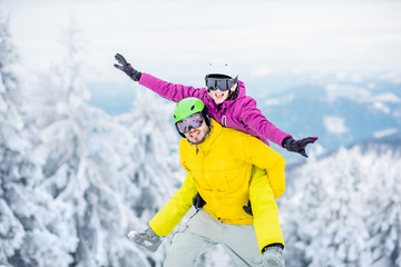 Young couple in snowboarding clothes having fun during the winter vacation on the snowy mountains
