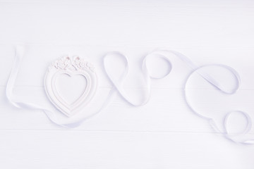 Top view Love word lettering written with white satin ribbon and photo frame in shape of heart on the white wooden background. Flat lay. Love expression. Copy space.