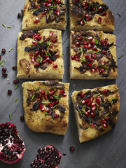 Overhead view of bread garnished with herbs and pomegranate seeds