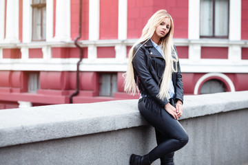 Fashion portrait of Beautiful young woman walking in the city. girl with perfect make-up,blond long hair,wearing a black hat and leather coat, blue shirt, posing in old city. Copy space.