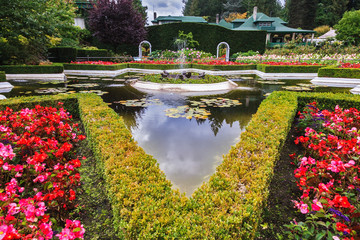 Exquisite fountain among the flower beds