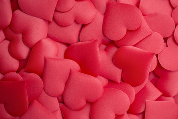 Decorative colourful sponge is small red heart background. Many colorful silk hearts - valentine background