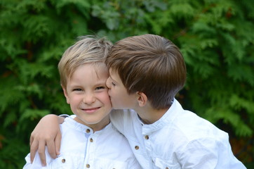 A portrait of two smiling happy boys in white shirts  having fun outdoors. Young Caucasian/European white siblings playing in the garden.
