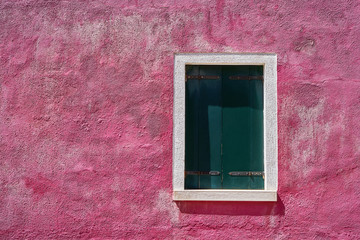 Window with closed green green shutter on bright pink wall. Italy, Venice, Burano island.