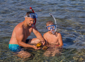 Father and sun diver find two big shells in the Aegean clear  sea.