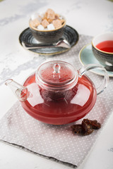 Serving table for breakfast, red tea in teapot and cup on a white table