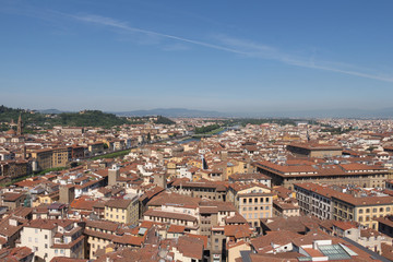 Florentine cityscape with red roofs and Arno river in a sunny day, Tuscany, Italy.