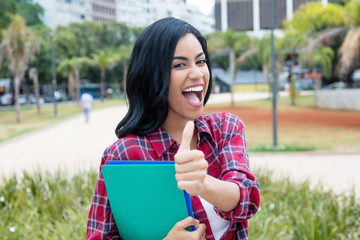 Successful native latin american female student showing thumb