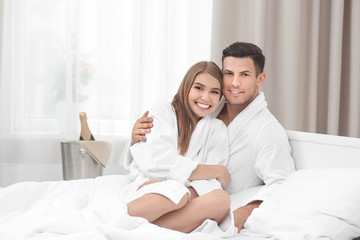 Young loving couple in bathrobes relaxing on bed at hotel