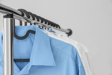 Rack with clean shirts in laundry, closeup