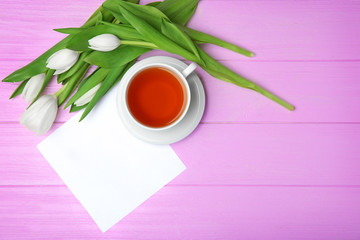 Tulips, card and cup of tea on pink wooden background