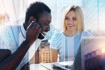 Favourite activity. Cheerful well-built afro-american man and a beautiful content blond woman wearing headphones and listening to music while sitting at the table with a laptop
