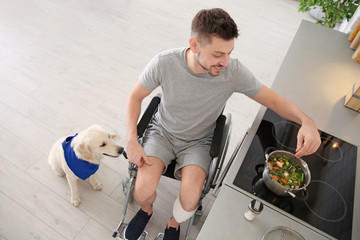 Man in wheelchair cooking with service dog by his side indoors