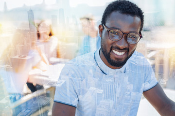 International student. Handsome male person keeping smile on his face and wearing stylish glasses while sitting against urban background