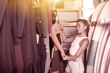 woman surfer choosing suit for surfing in the shop