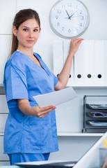 Female doctor near shelves in office