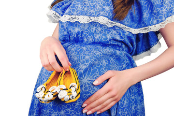 Pregnant woman female holding knitted needles with knitted mouse baby's bootees on isolated background