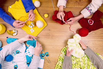 Dressmaker workplace. Group of four woman female knitting warm clothes by knitted needles on wooden background
