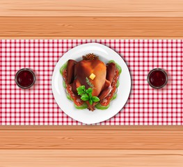 Roasted turkey bird on white plate with fork and knife on wooden table